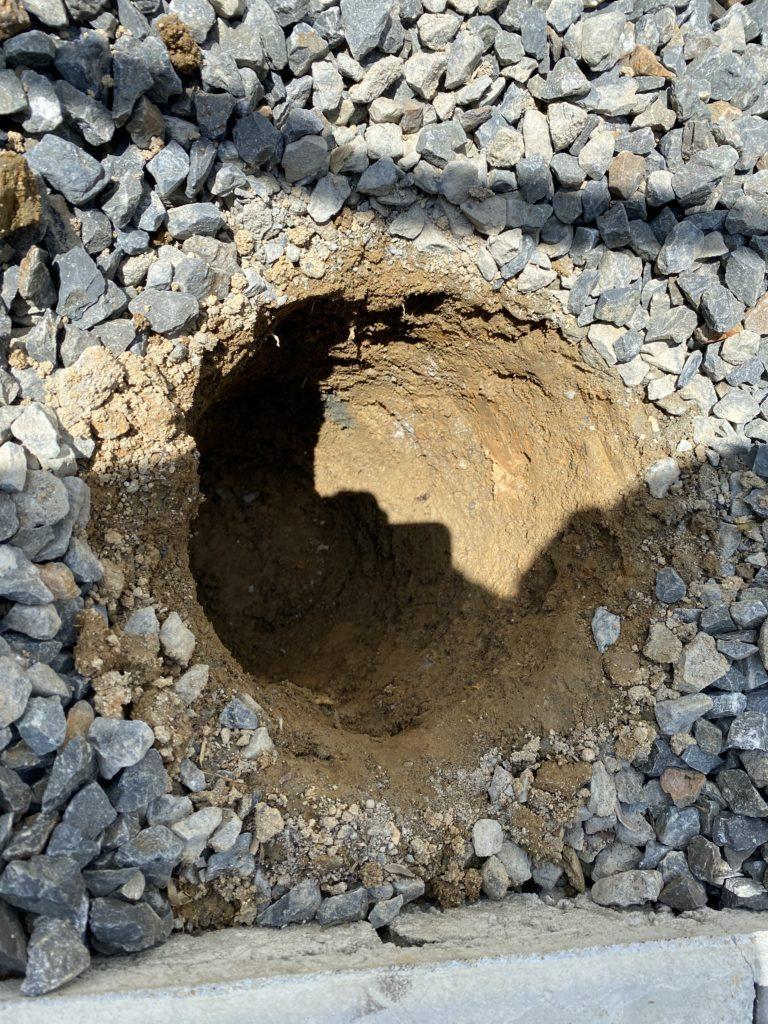 自宅の庭に鉄棒の支柱を埋めるための穴を掘る